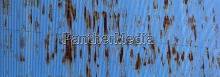 blue tin wall with rust markings