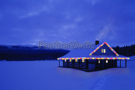 cabin with christmas lights and snowy