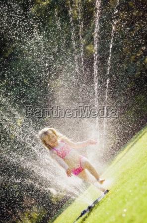 child runs through sprinkler