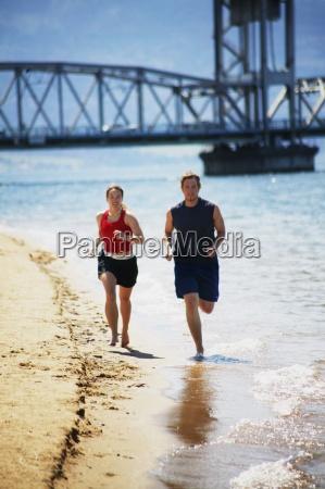couple jog together along the shore