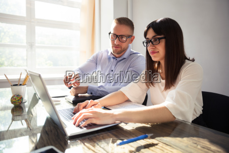 two businesspeople using laptop