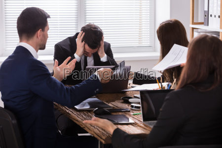 businesspeople blaming depressed male colleague