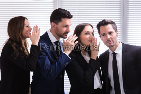 businesspeople gossiping into young mans ear