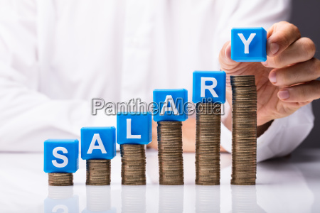 person making salary word on stacked
