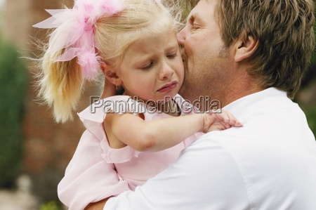 father comforts daughter after a fall