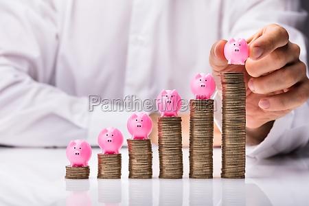 person placing piggybank on increasing stacked