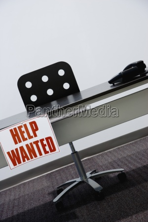 help wanted sign hanging off a