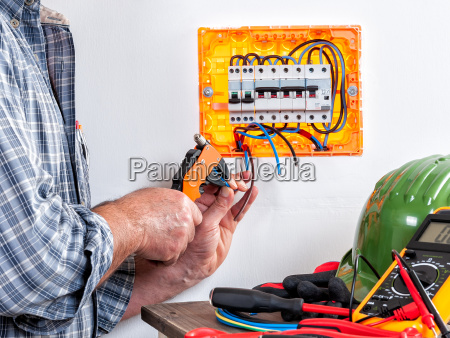 electrician at work on cables with