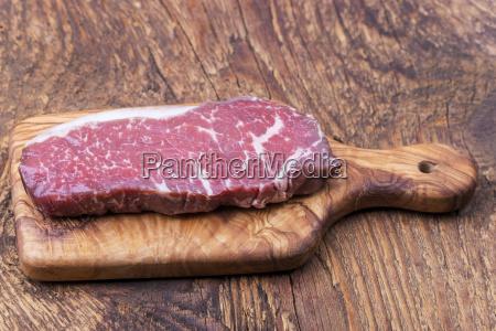 raw steak on olive wood