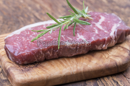 raw steak on olive wood