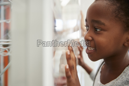 young black girl looking closely at