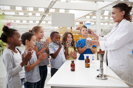 lab technician showing excited kids a