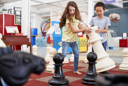 two children playing giant chess at