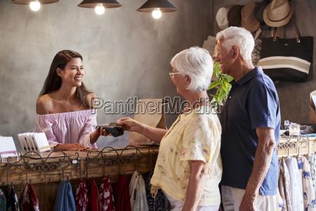 senior customers buying goods in store