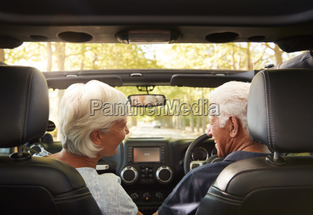senior couple drive open top car