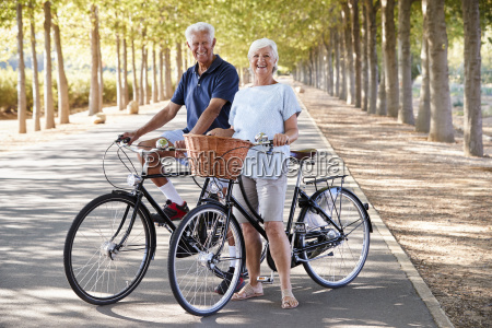 portrait of smiling senior couple cycling