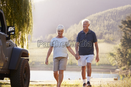 senior couple walking by lake at