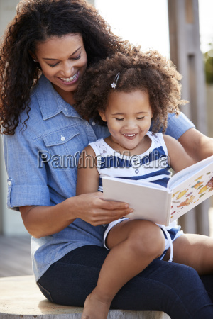 young black girl reading book sitting