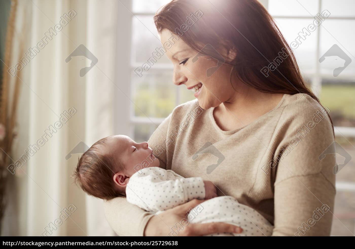 Loving mother cuddling newborn baby at 25729638