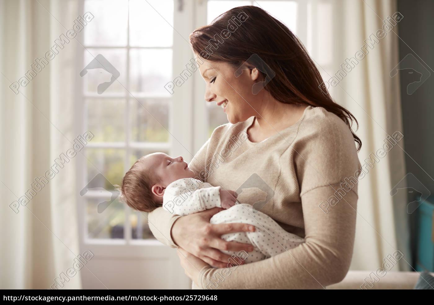 Royalty free photo 25729648 loving mother cuddling newborn baby at home