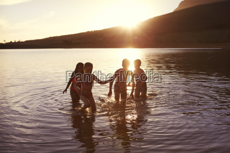 children with friends enjoying evening swim