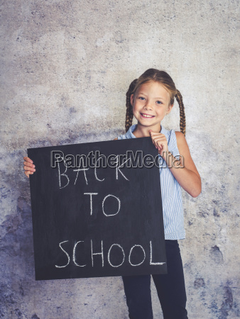 blond schoolgirl is holding blackboard with