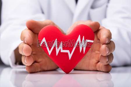 human hand protecting heart with heartbeat