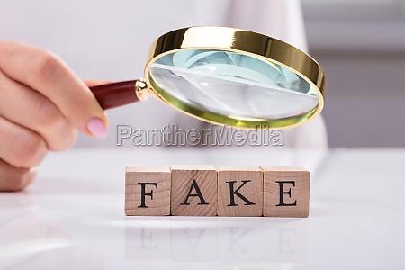 businesswoman examining blocks showing fake word