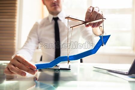 businessperson manipulating blue arrow