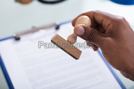 hand holding stamp over the document
