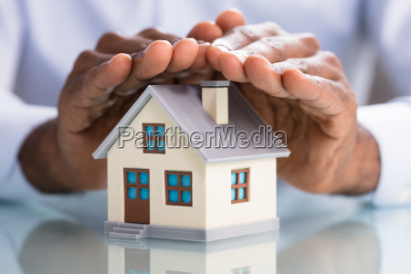 person protecting miniature house