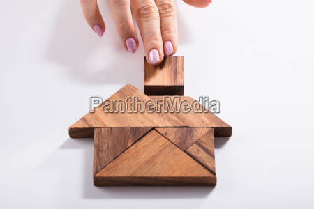 woman building house with wooden tangram