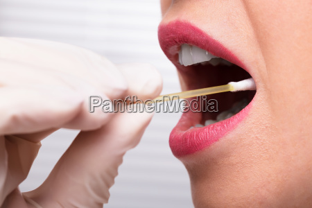 dentists hand taking saliva test from