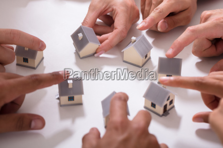group of people touching miniature house