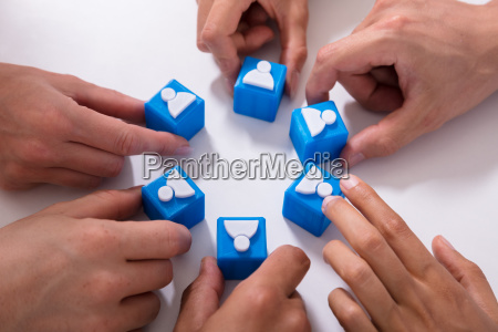 businesspeople holding cubic blocks with human