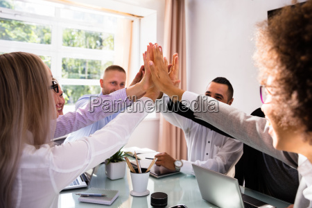group of businesspeople giving high five