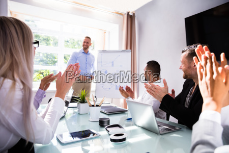 businesspeople applauding their colleague after presentation