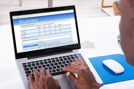 man filling survey form on laptop