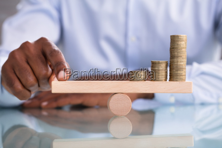 businessman balancing the coin stack on