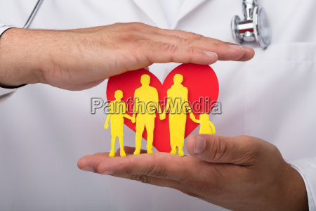 doctor protecting heart with family figures