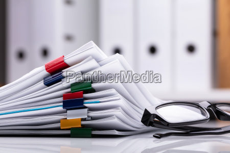 stacked documents and eyeglasses