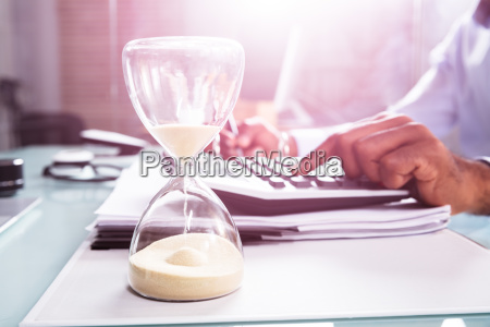 hourglass in front of businessperson calculating