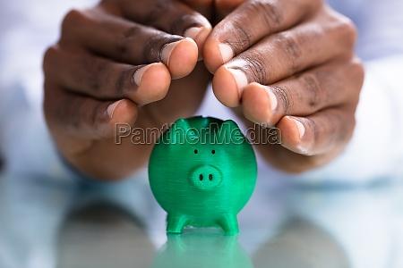 hand covering the green piggybank