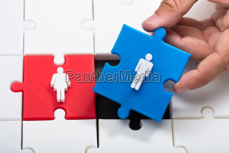person placing male piece beside female