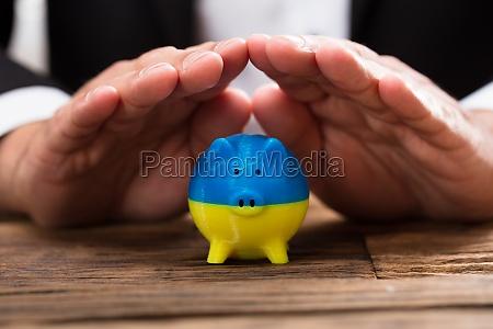 businessperson protecting piggybank