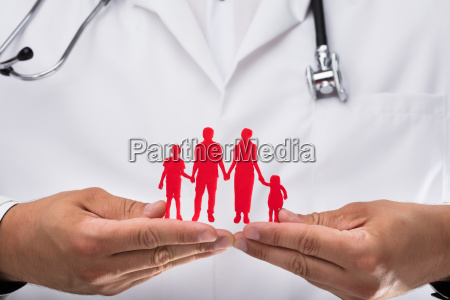 doctor holding family figures