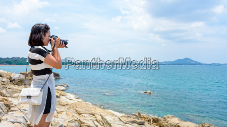 young woman photography near the sea