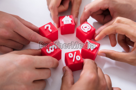 people holding red cubic blocks with