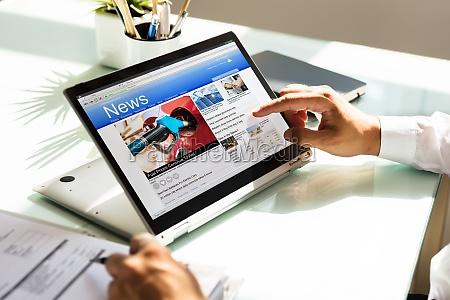 forretningsmand kontrol online nyheder pa laptop