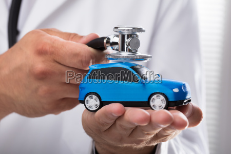 doctor examining blue car